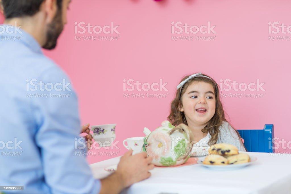 ハンサムの父親は、彼女のピンクのベッドルームで就学年齢娘と一緒にお茶会を楽しんでいます ストックフォト