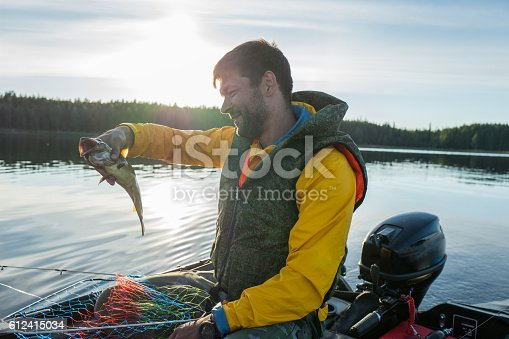 932662672istockphoto Handsome fisherman catched a haddock in the sea 612415034
