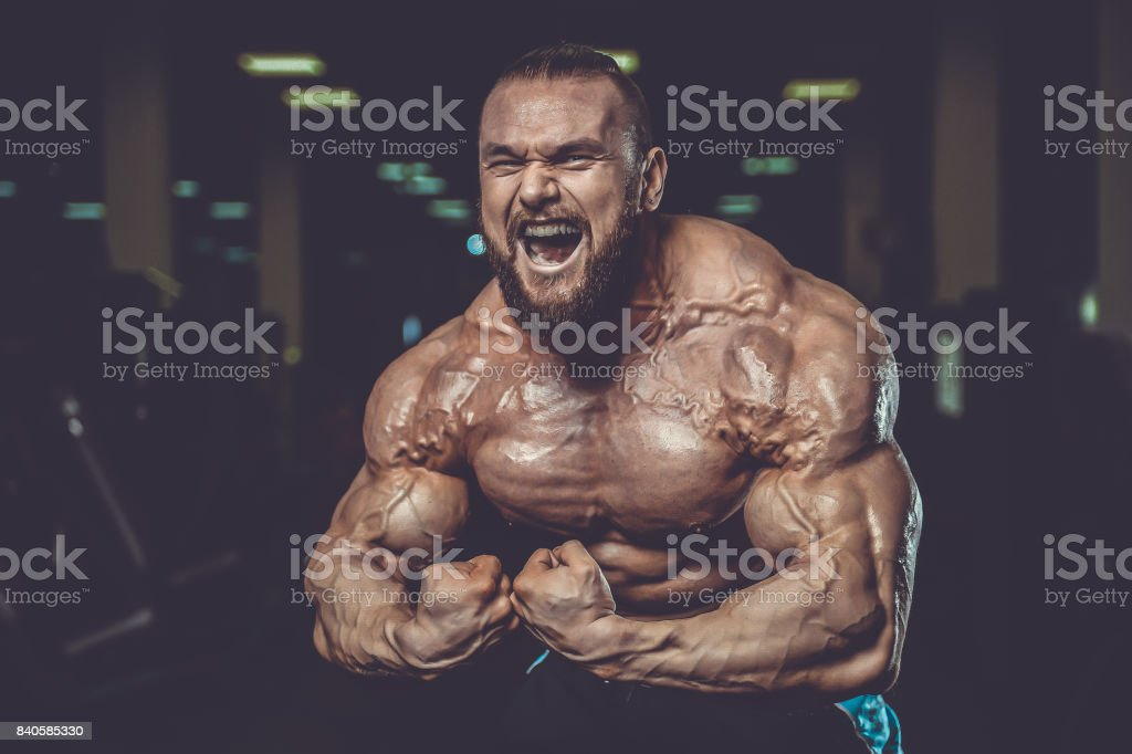 Handsome fit caucasian muscular man flexing his muscles in gym stock photo
