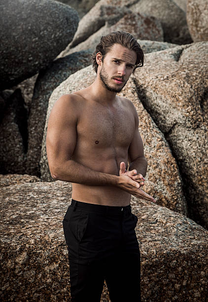 handsome fit man handsome man,with strong fit body,staying in front in a rocky location,looking at the camera shirtless male models stock pictures, royalty-free photos & images