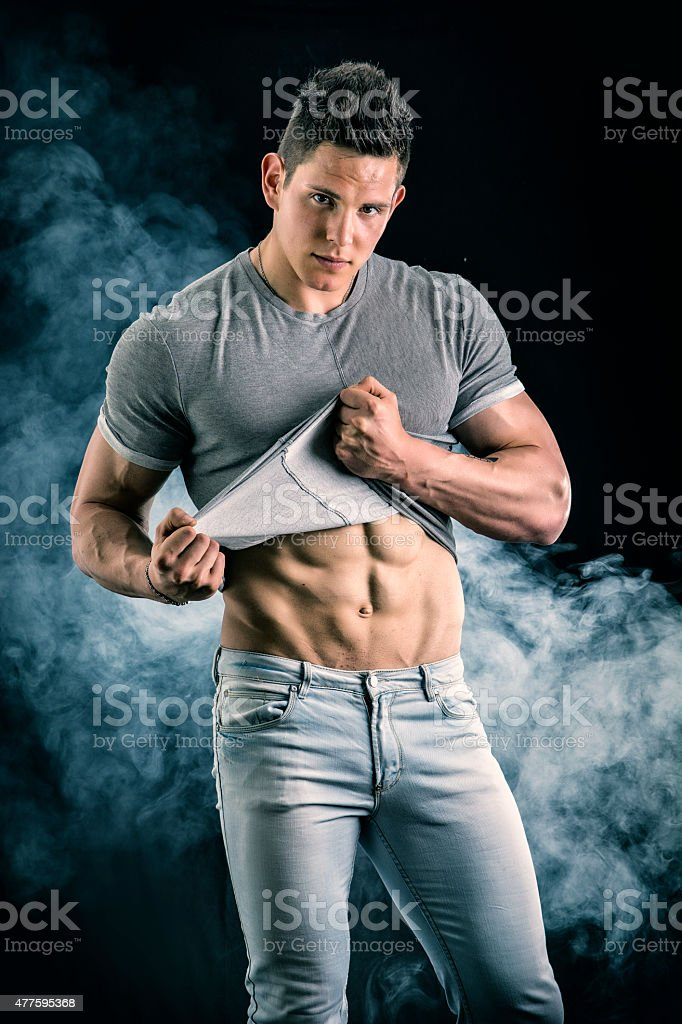Handsome, fit young man pulling up t-shirt revealing abs stock photo