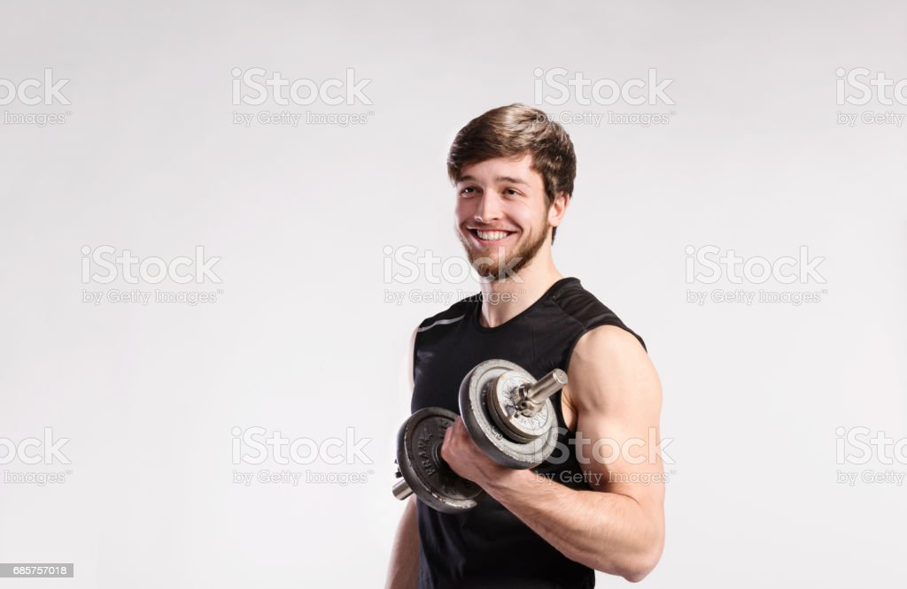 Handsome fitness man holding dumbbell, studio shot. ロイヤリティフリーストックフォト