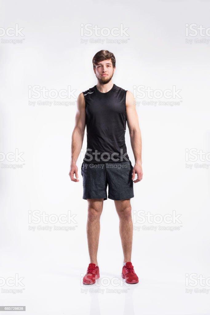 Handsome fitness man in black sleeveless shirt, studio shot. royalty-free stock photo