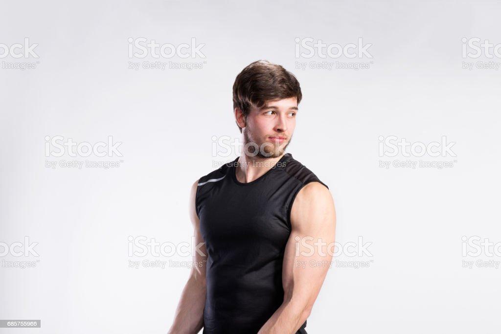 Stilig fitness mannen i svart ärmlös skjorta, studio skott. royaltyfri bildbanksbilder