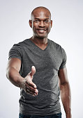 Single handsome young Black male fitness trainer in gray compression shirt reaching out toward camera to shake hands over neutral background
