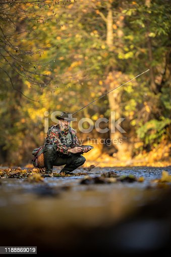 Handsome fly fisherman working the line and the fishing rod while fly fishing on a splendid mountain river for rainbow trout