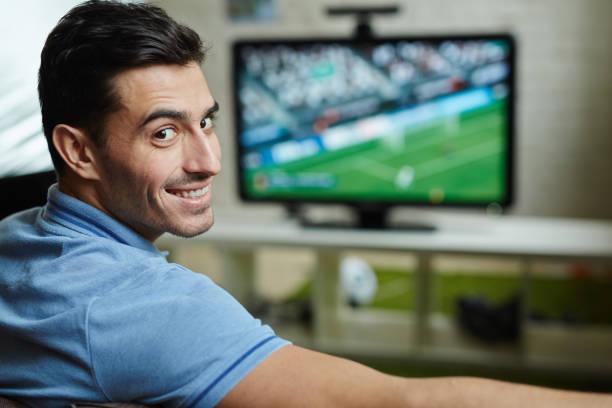 Aficionado al fútbol guapo en casa - foto de stock