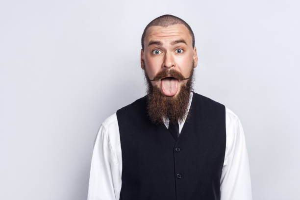 Handsome funny businessman Crazy Funny face. Handsome businessman with beard and handlebar mustache looking at camera with tongue out. studio shot, on gray background. protruding stock pictures, royalty-free photos & images