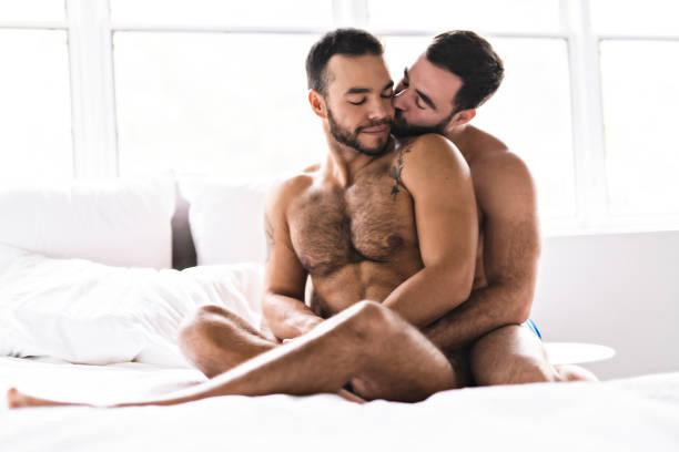 una bella coppia di uomini gay a letto insieme - a petto nudo foto e immagini stock