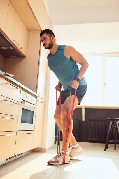 Handsome gentleman doing exercise with elastic fitness band stock photo