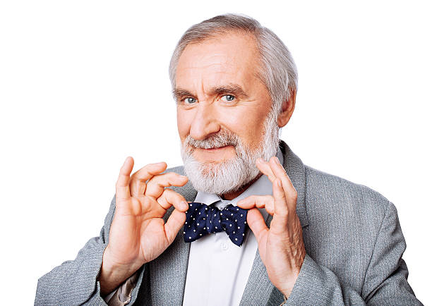 Handsome gentleman with a bow tie Senior gentleman adjusting his bow tie fine art portrait stock pictures, royalty-free photos & images