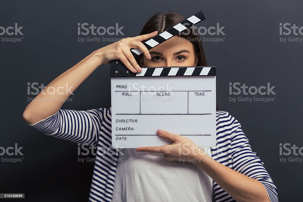 Handsome girl with clapperboard stock photo