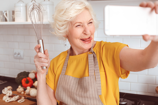 Handsome grandmother makes funny selfie with a whisk in the kitchen.