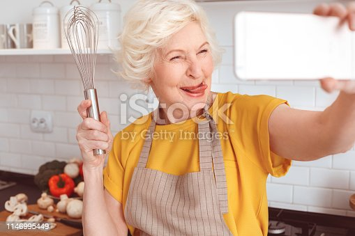 Tongue out, crazy face. Handsome grandmother makes funny selfie with a whisk in the kitchen. Indoor, studio shoot, kitchen interior