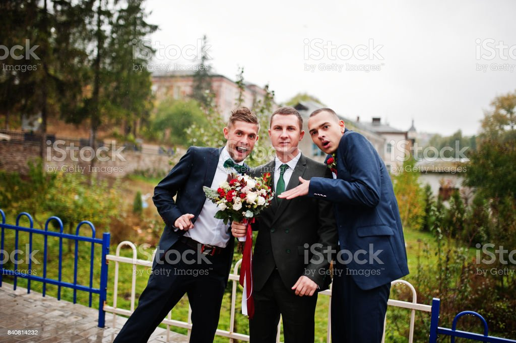 Handsome groom and his fellow groomsmen having fun outside on a rainy wedding day. stock photo