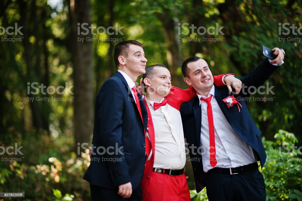 Handsome groom and his groomsmen posing in the forest on the wedding day. stock photo