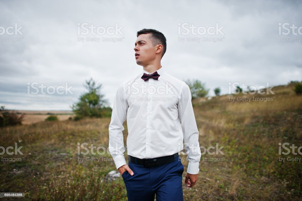Handsome groom in the middle of the meadow surrounded by tall grass, bushes and rocks. stock photo