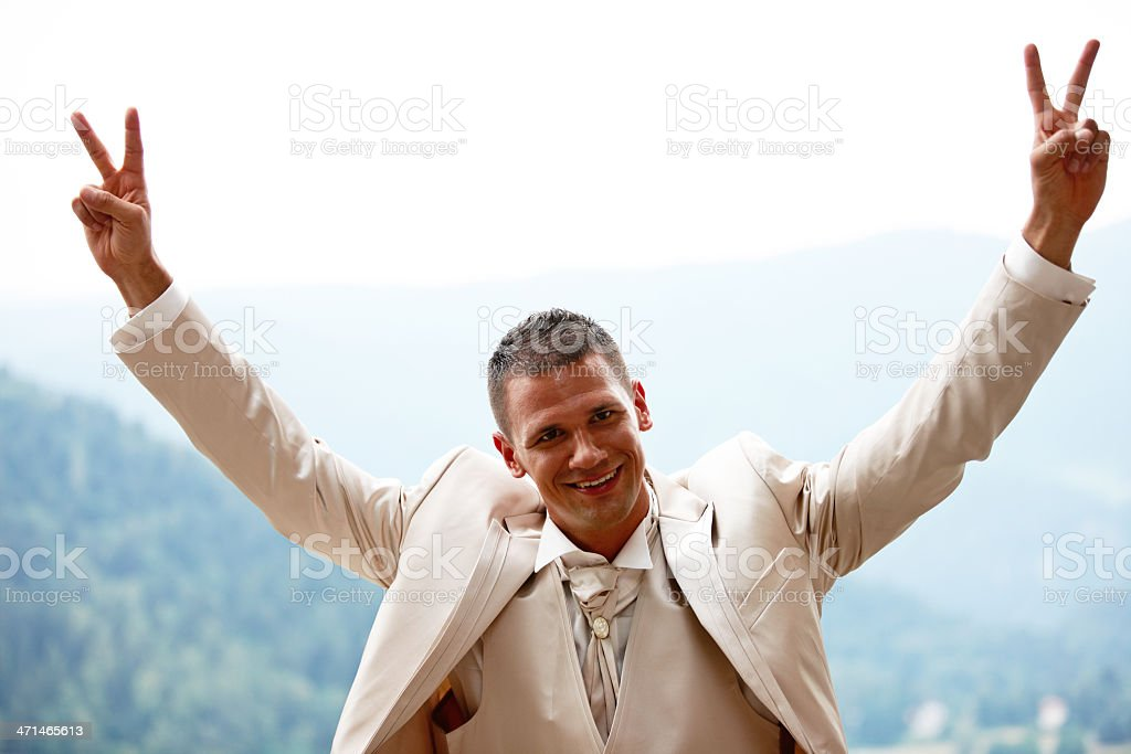 Handsome groom in wedding suit hands up royalty-free stock photo