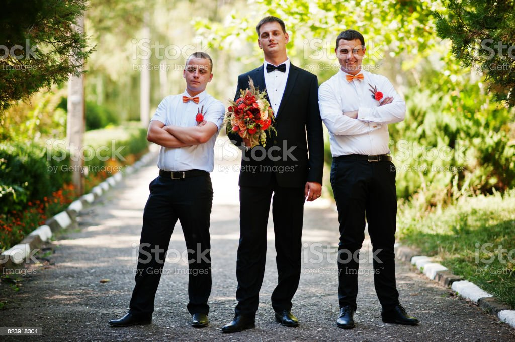 Handsome groom walking with his bestmen or groomsmen in the park on a wedding day. stock photo