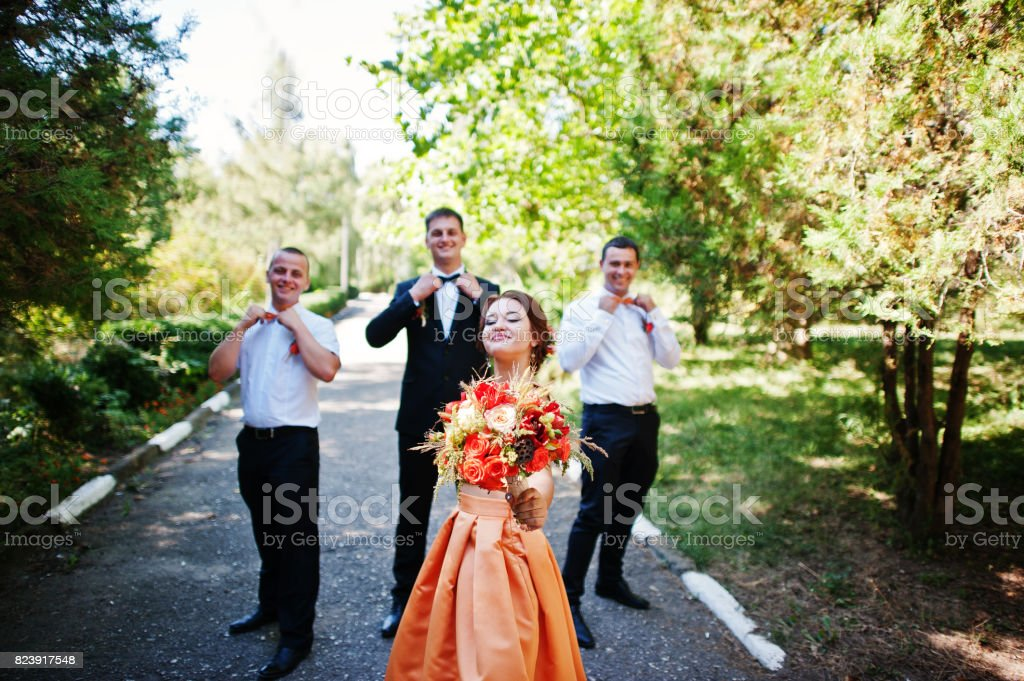 Handsome groom walking with his groomsmen and a bridesmaid in the park on a wedding day. stock photo