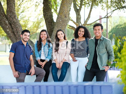 A handsome group of latin students outside smiling at the camera wearing casual clothing.