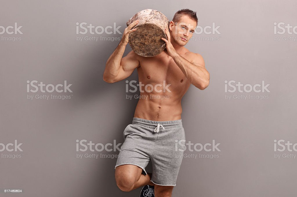 Handsome guy carrying a log on his shoulder stock photo