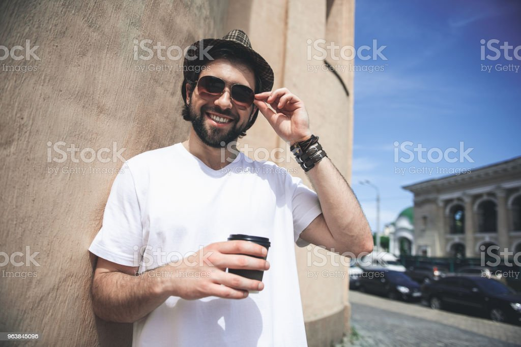 Handsome guy consuming hot drink on walk - Royalty-free Adult Stock Photo
