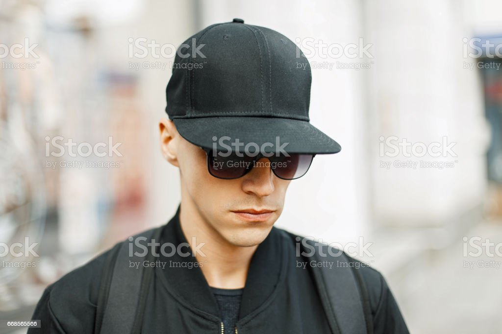 5961c429 Handsome guy in a black baseball cap and stylish black clothes, outdoors  royalty-free
