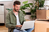 istock Handsome guy in his new apartment holding a laptop 1200276194