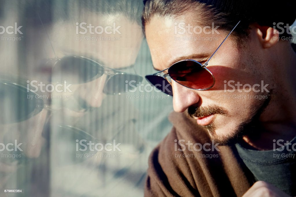 Handsome guy in sunglasses on the streets of a big city. Reflection. stock photo
