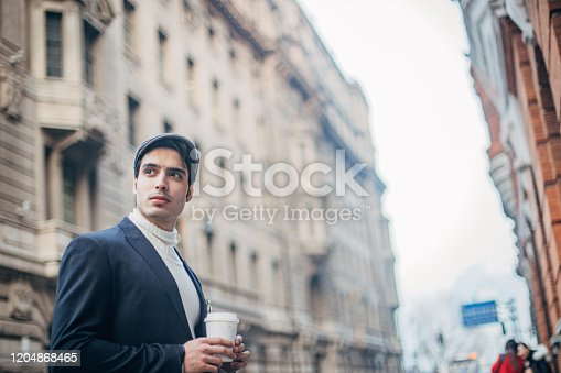 Handsome, elegant man with hat is drinking takeaway coffee on the street.