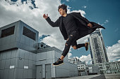Stylish young man in ripped jeans making jump as if he running on air