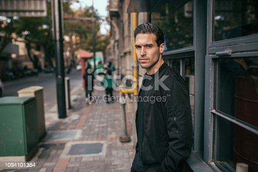 One young handsome guy wearing black outfit, waiting for someone.