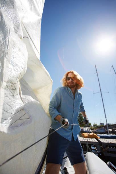 hübscher kerl segeln vorbereiten - segelhandschuhe stock-fotos und bilder