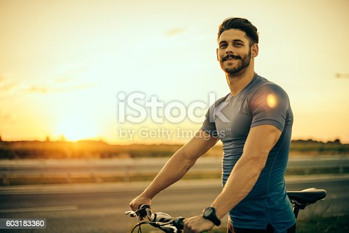 istock Handsome guy riding mountain bike in sunset 603183360