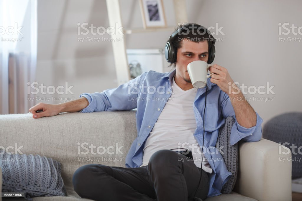 Handsome guy sitting on sofa with headphones royalty-free 스톡 사진