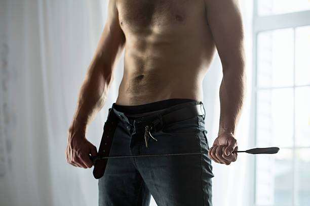 Handsome guy topless with whip BDSM stock photo