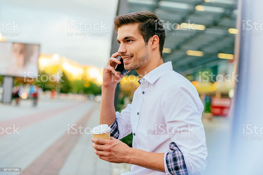 Handsome guy using phone and drinking coffee photo libre de droits