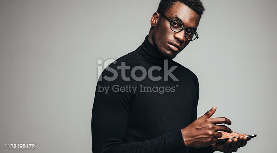 African man in black polo t-shirt using his smart phone and looking at camera. Handsome guy with a mobile phone on gray background.