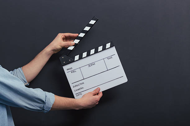 Handsome guy with clapperboard stock photo