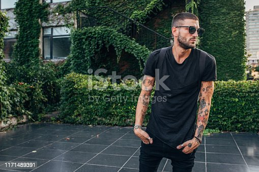 Handsome man with tattoos and backpack standing outdoors and looking away.