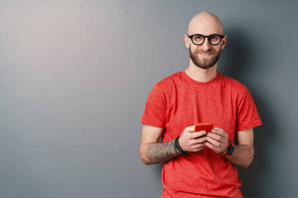 Handsome hairless Caucasian man with beard, glasses, red T-shirt holding smartphone in his tattooed arms on gray studio background Smiling hairless Caucasian man with beard, glasses, red T-shirt texting while holding smartphone in his tattooed arms and looking at camera, over gray studio background with copy space. red shirt stock pictures, royalty-free photos & images