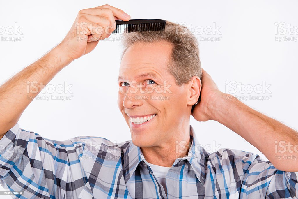 Handsome happy aged man combing his hair stock photo