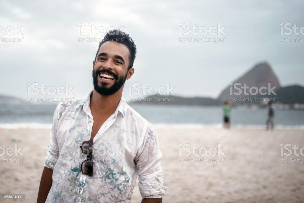 feliz barbudo brasileiro jovem bonito na praia no Rio de Janeiro - foto de acervo