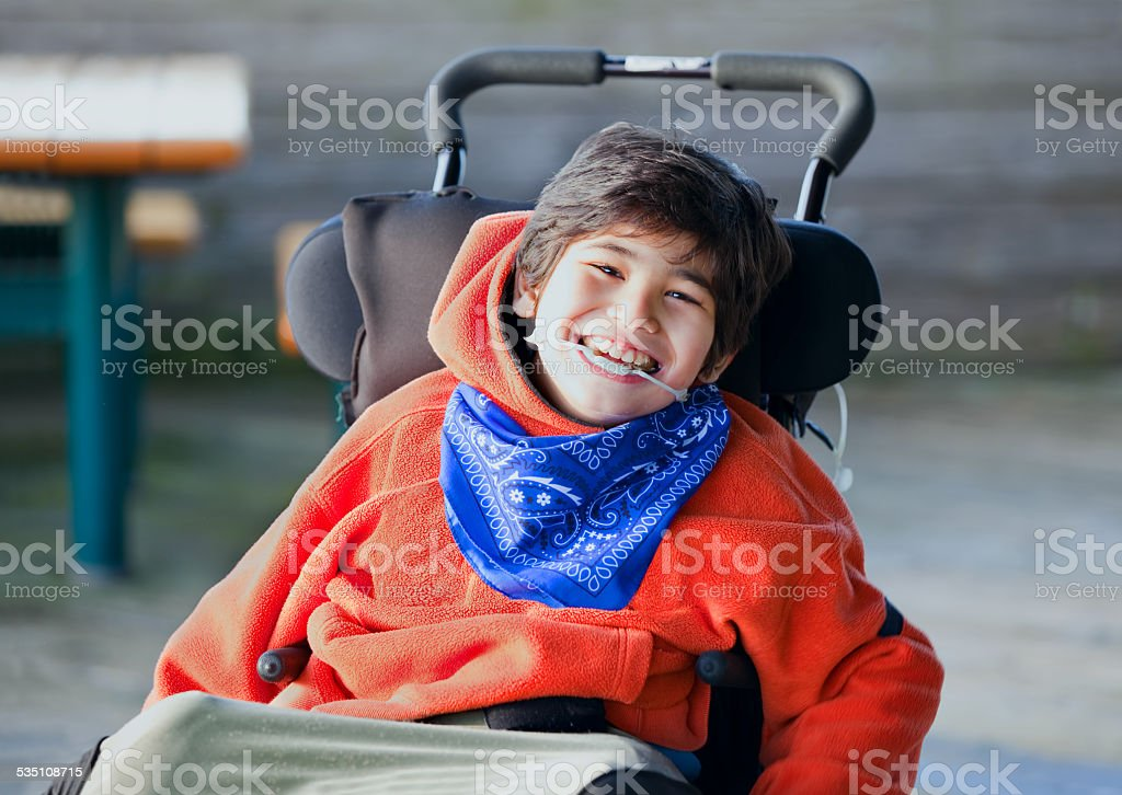 Handsome, happy biracial eight year old boy smiling in wheelchair stock photo