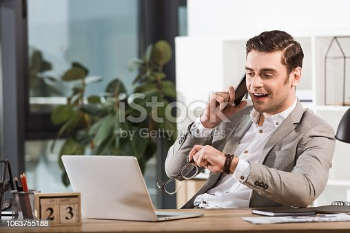 handsome happy businessman talking by phone at workplace in office and looking at laptop screen