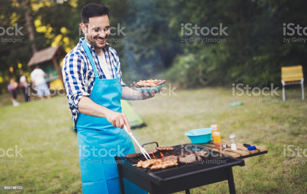 Handsome  happy male preparing barbecue outdoors for friends stock photo