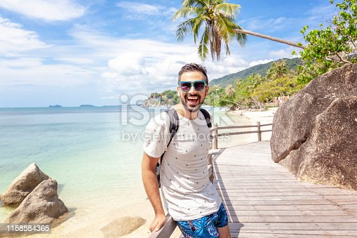 Handsome happy man wearing white T-shirt at the sea or the ocean background. Travel vacation holiday. Man walking at the sea, enjoy tropical season. Relax mix raced  adult man