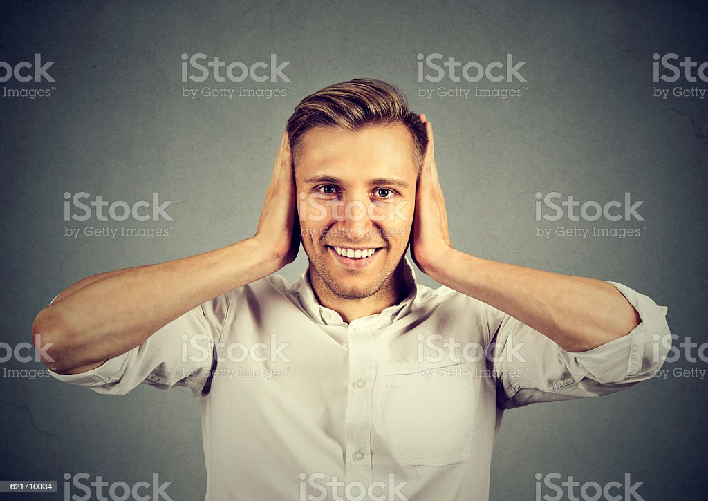 Handsome happy young man covering his ears stock photo