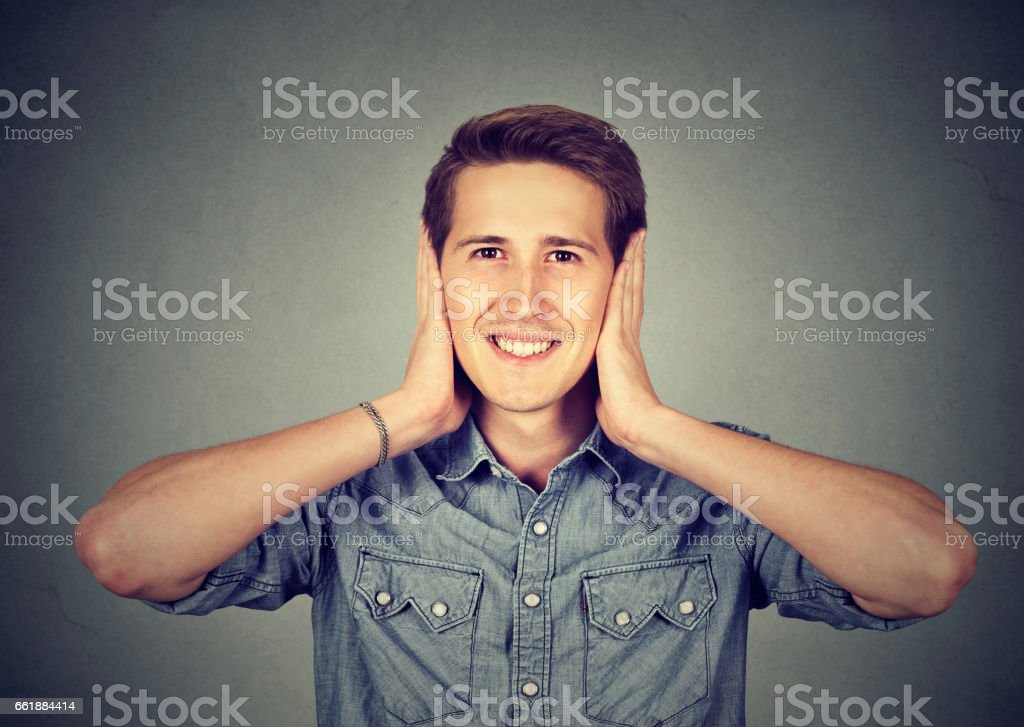 Handsome happy young man covering his ears with hands stock photo